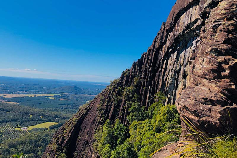 Sheer rock face with view of the Beerwah Conservation Reserve
